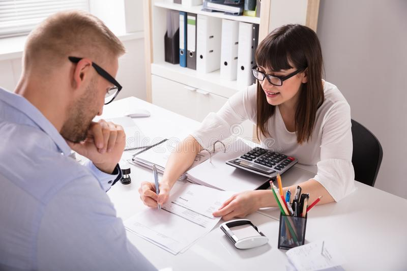 Financial Advisor Discussing Invoice With Her Client. Young Financial Advisor Discussing Invoice With Her Client At Workplace royalty free stock images