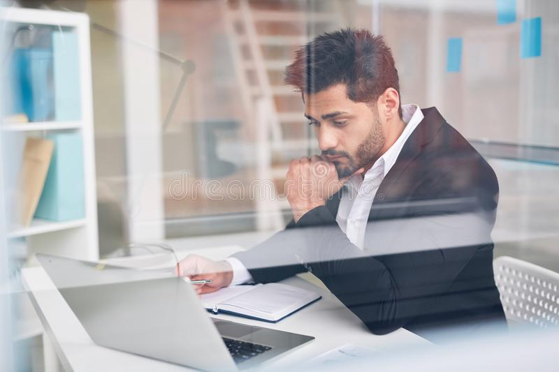 Man contemplating. Young financier concentrating on working over online project or reading data stock photo