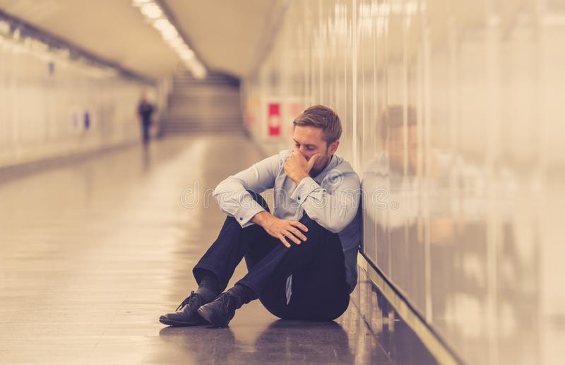 Young fired business man lost in depression crying abandoned sitting on ground subway suffering emotional pain royalty free stock images