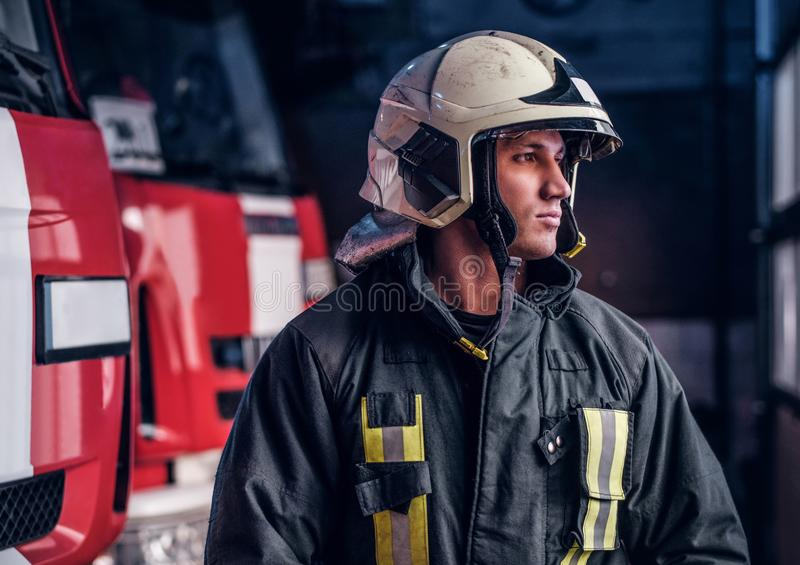 Young fireman wearing protective uniform standing next to a fire engine in a garage of a fire department. Brave young fireman wearing protective uniform standing stock photography