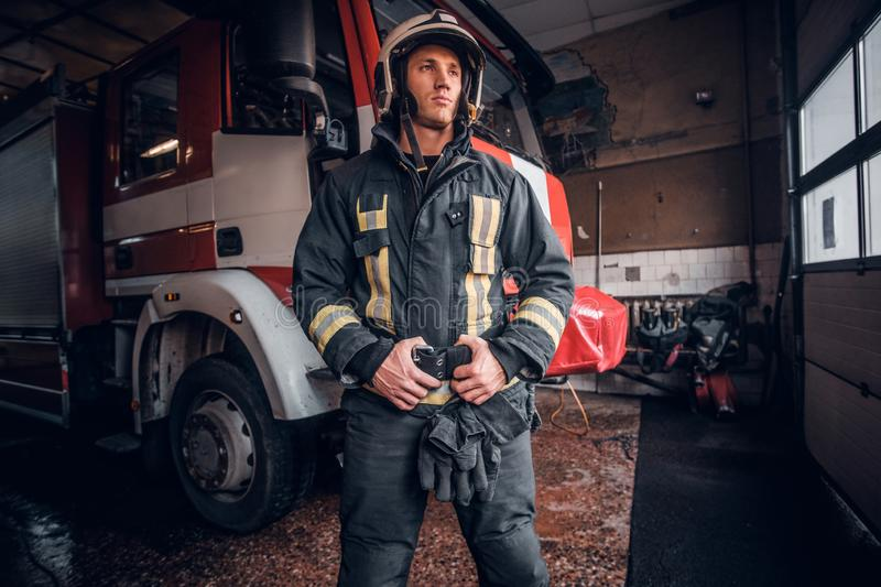 Young fireman wearing protective uniform standing next to a fire engine in a garage of a fire department stock photo