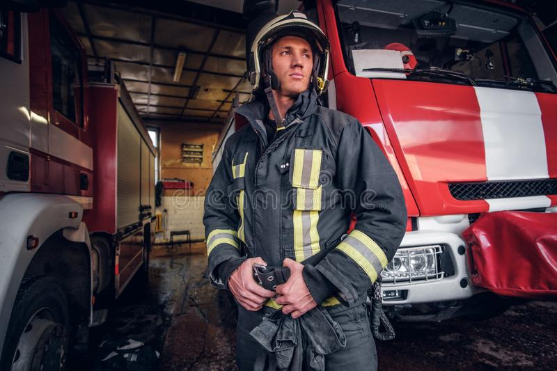 Young fireman wearing protective uniform standing next to a fire engine in a garage of a fire department. Portrait of a brave young fireman wearing protective royalty free stock images