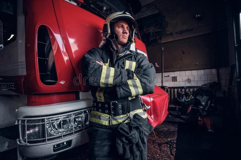 Young fireman wearing protective uniform standing next to a fire engine in a garage of a fire department royalty free stock photos