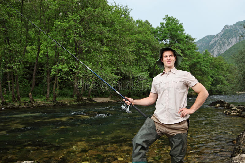 Download Young Fisherman Fishing On A River Stock Photo - Image of outdoor, male: 19695968