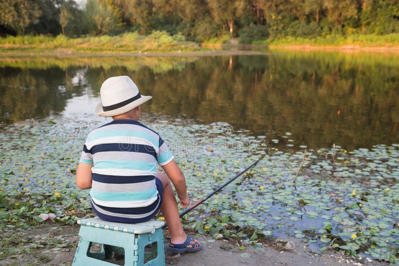 Young fisherman on the lake stock photo