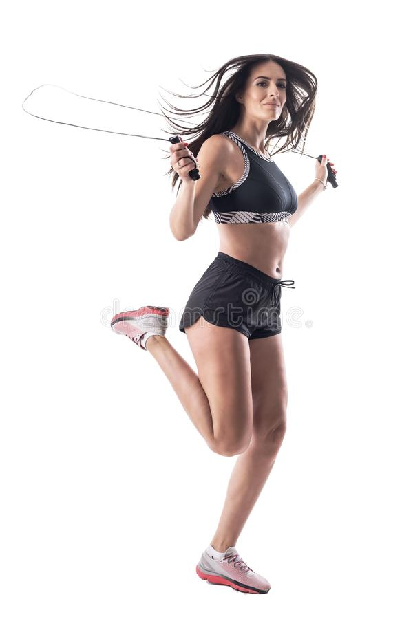 Young fit active brunette latin woman doing jumping or skipping rope exercises. Full body isolated on white background royalty free stock photo