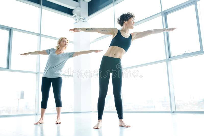 Arm stretching. Young fit active women and her mature groupmate in sportswear outstretching their arms while exercising in gym royalty free stock image