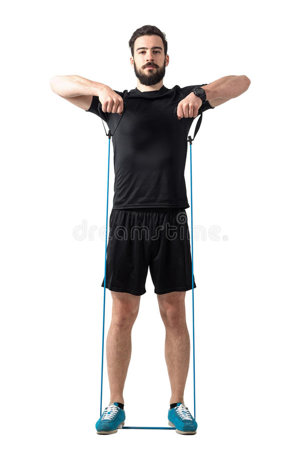 Young fit athletic man shoulder exercising with resistance bands. Full body length portrait isolated over white studio background stock image