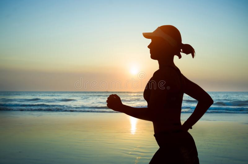 Young fit and attractive woman in American cap training on sunset beach doing running fitness workout under a beautiful sky in royalty free stock images