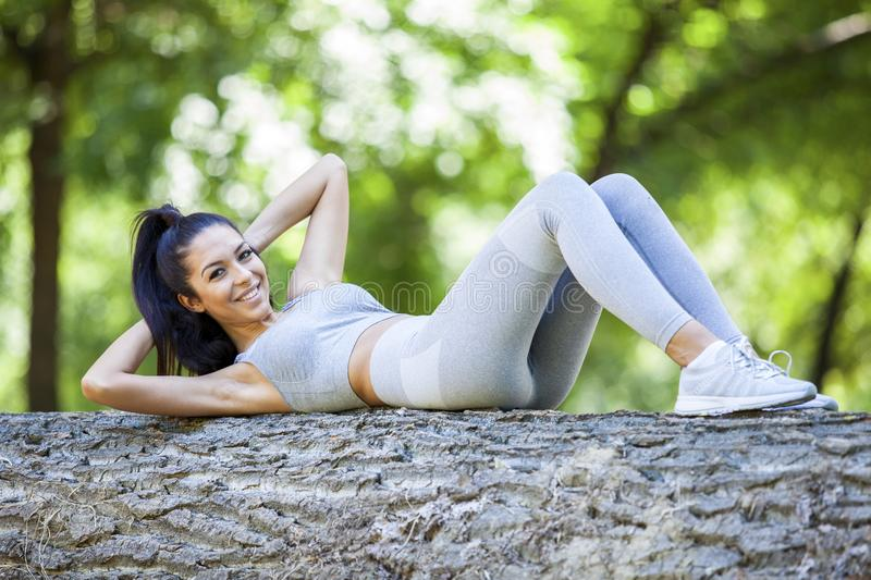 Young fit beautiful girl doing sit ups on a tree log. Outdoor on a grass field in forest during summer sunny day stock photo