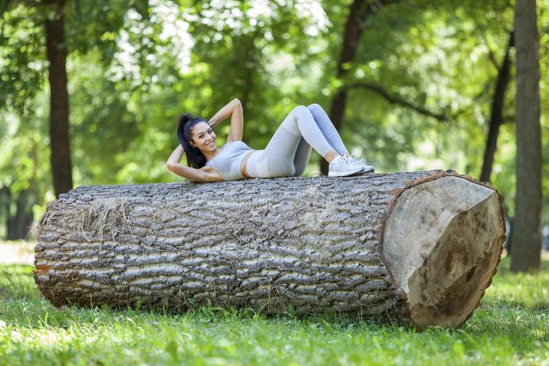 Young fit beautiful girl doing sit ups on a tree log. Outdoor on a grass field in forest during summer sunny day royalty free stock photo