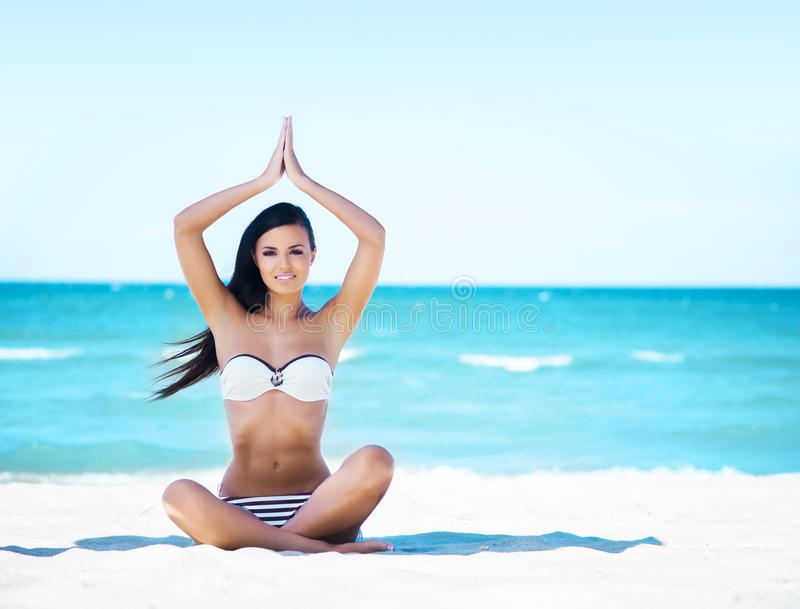 Young, fit and beautiful girl meditating on the beach stock images
