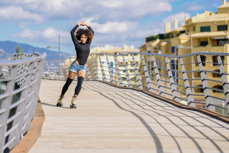 Afro hairstyle woman on roller skates riding outdoors on urban b. Young fit black woman on roller skates riding outdoors on urban bridge with open arms. Smiling stock images