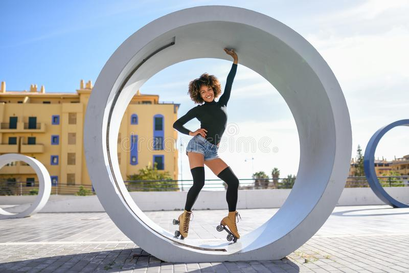 Young fit black woman on roller skates riding outdoors on urban street. Smiling girl with afro hairstyle rollerblading on sunny stock photos