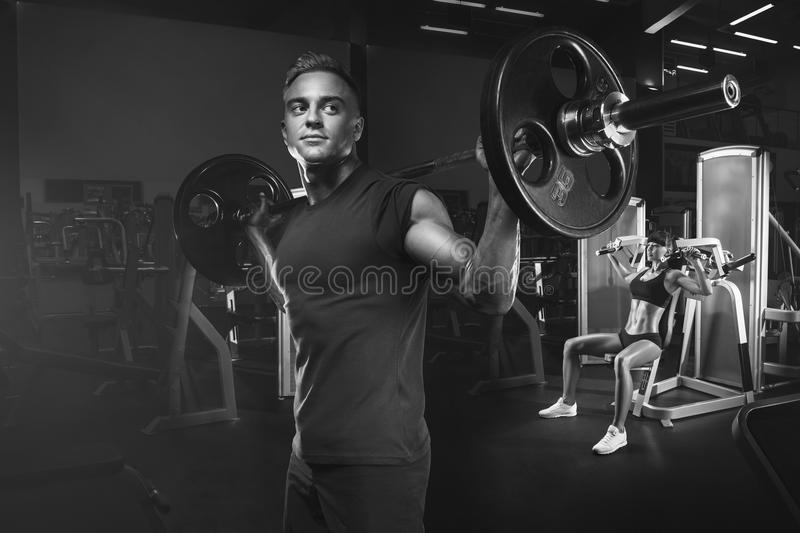 Young and fit couple in the gym doing workout. Group of women and men bodybuilders training on special sport equipment in the gym. Sport, bodybuilding stock photos