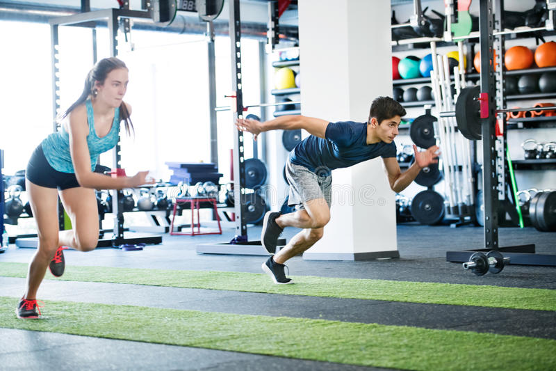 Young fit couple in gym fast running. Young men and women doing intense training session. Sports training in the gym stock photography