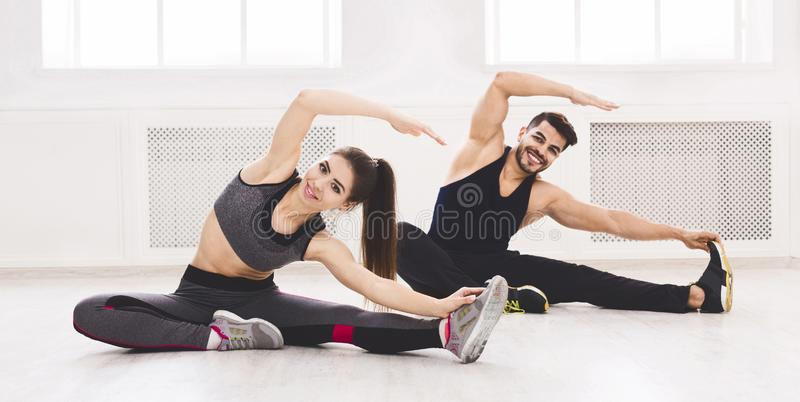 Young fit couple stretching on the floor in studio. Young fit couple stretching on the floor in light studio, panorama, free space stock photography