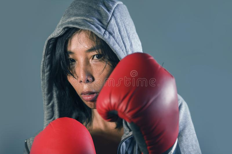 Young fit and healthy Asian Korean boxer woman in fitness top hoodie and boxing gloves posing cool badass attitude angry and defia royalty free stock photography