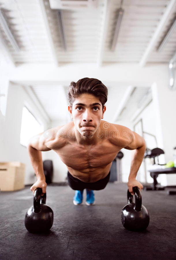 Young fit hispanic man in gym doing push ups on kettlebells royalty free stock photo