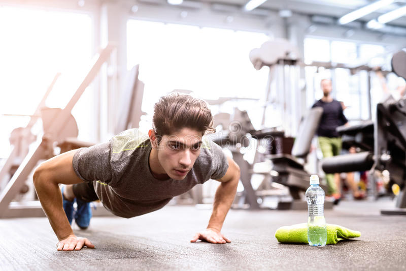 Young fit hispanic man in gym doing push ups. Fit hispanic man in gym training, doing push ups royalty free stock image