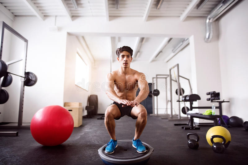 Young fit hispanic man in gym doing squats on fitness ball stock images