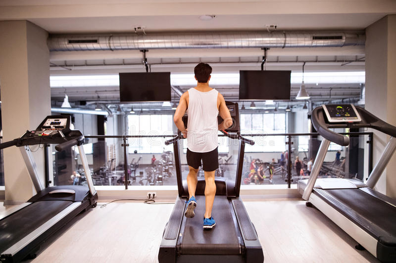 Young fit hispanic man in gym running on treadmill. royalty free stock photo