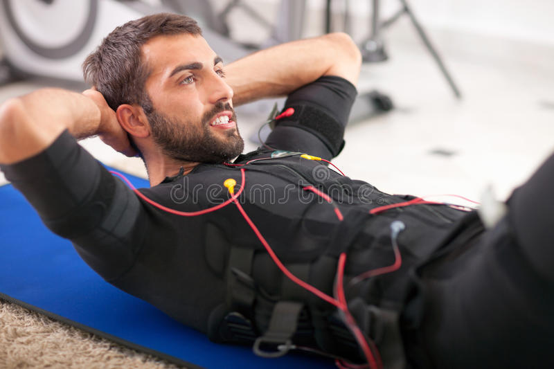 Young fit man exercise on electro muscular stimulation machine stock images