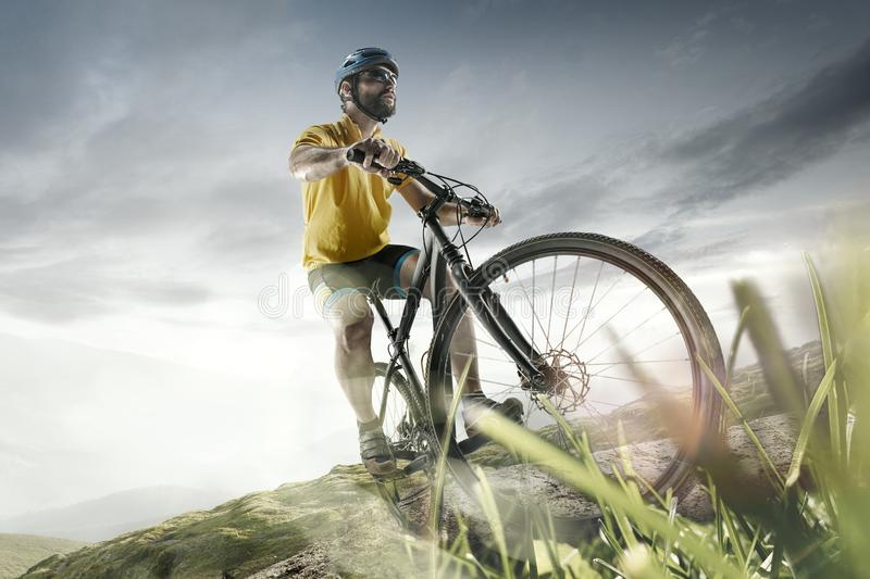 The young fit men in helmet conquering mountains on a bicycle. royalty free stock photos