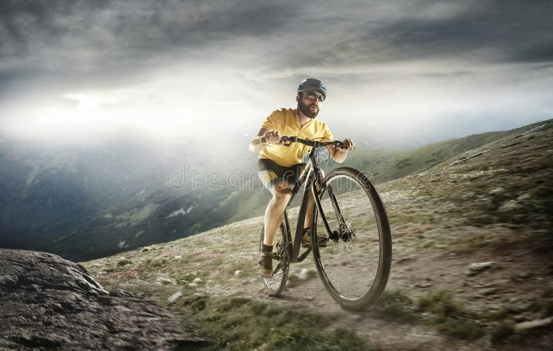The young fit men in helmet conquering mountains on a bicycle. stock images