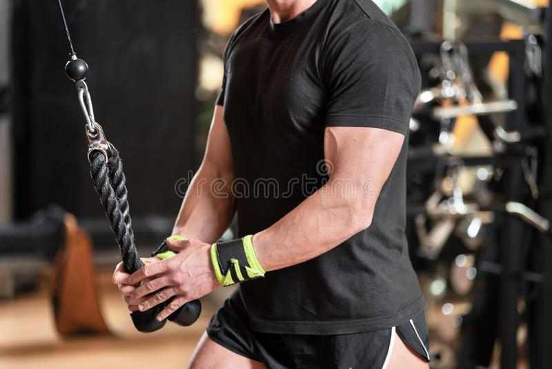 Young fit muscular man close up doing triceps pull down rope extension exercise in modern fitness center. stock photo