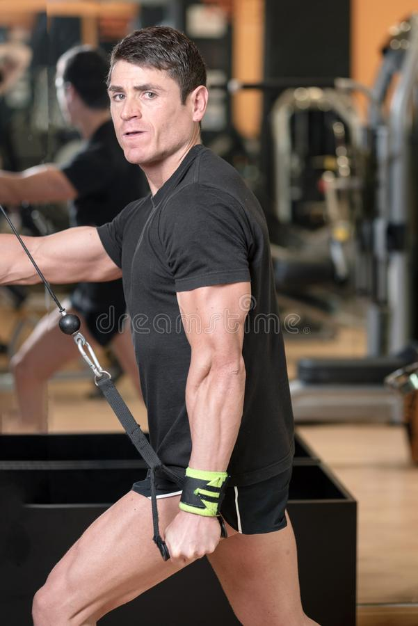 Young fit muscular man close up doing triceps pull down rope extension exercise in modern fitness center. stock photos