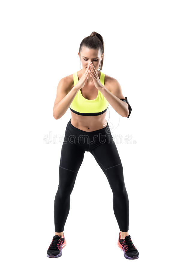 Young fit pretty female jogger warming up while doing quick feet shuffle exercise. Full body length portrait isolated on white studio background stock image