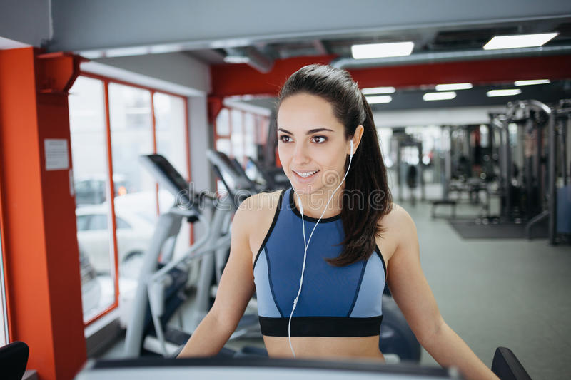 Young fit pretty woman doing exercises on the treadmill royalty free stock images