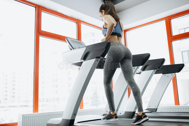Young fit pretty woman doing exercises on the treadmill stock photo