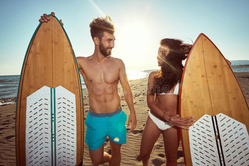 Young fit, sexy couple, talking on a beach, holding surfboards stock photography