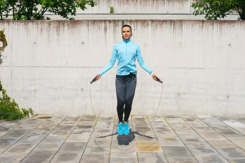 Young, fit and sporty woman jumping with a skipping rope. Fitness, sport, urban jogging and healthy lifestyle concept. Young, fit and sporty girl jumping with a royalty free stock photography