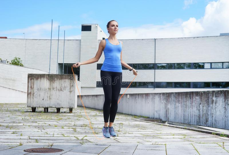 Young, fit and sporty girl jumping with a skipping rope. Fitness, sport, urban jogging and healthy lifestyle concept royalty free stock image