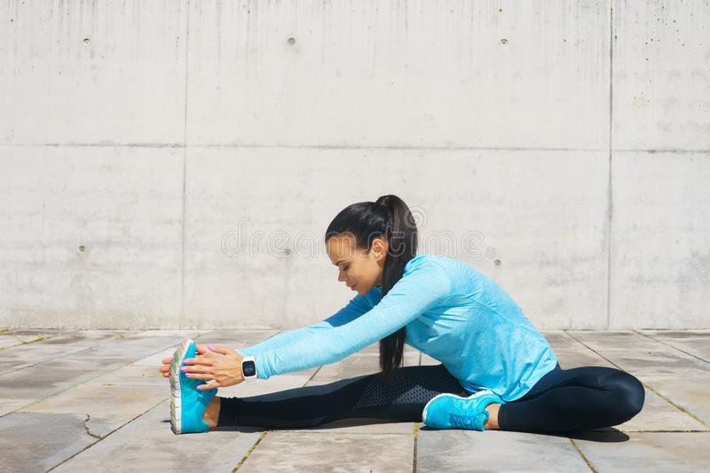 Young, fit and sporty girl stretching. Fitness, sport, urban jogging and healthy lifestyle concept. Young, fit and sporty girl stretching in the street. Fitness royalty free stock image
