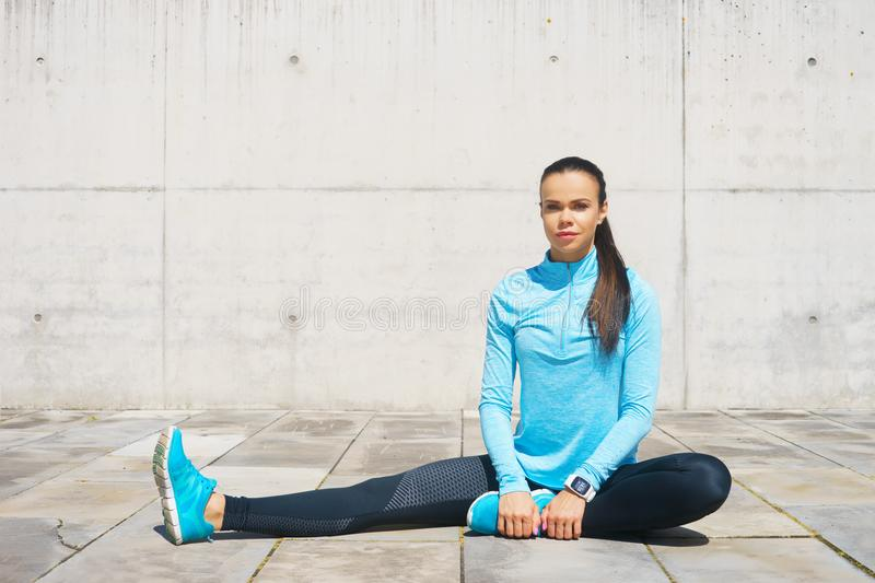Young, fit and sporty girl stretching. Fitness, sport, urban jogging and healthy lifestyle concept. Young, fit and sporty girl stretching in the street. Fitness stock images