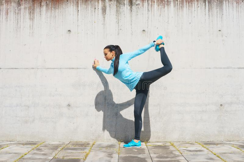 Young, fit and sporty girl stretching. Fitness, sport, urban jogging and healthy lifestyle concept. Young, fit and sporty girl stretching in the street. Fitness stock photos