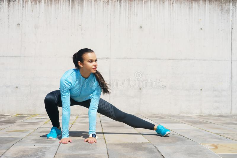Young, fit and sporty girl stretching. Fitness, sport, urban jogging and healthy lifestyle concept. Young, fit and sporty girl stretching in the street. Fitness stock image