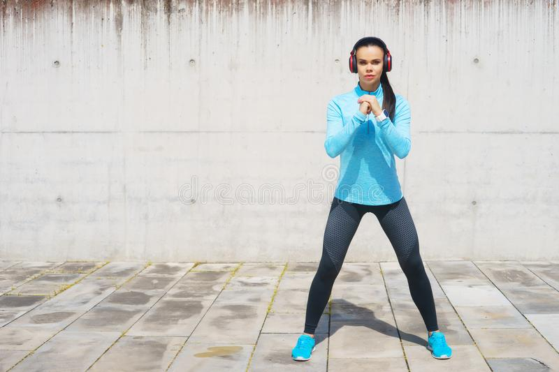 Young, fit and sporty girl stretching. Fitness, sport, urban jogging and healthy lifestyle concept. Young, fit and sporty girl stretching in the street. Fitness royalty free stock photography