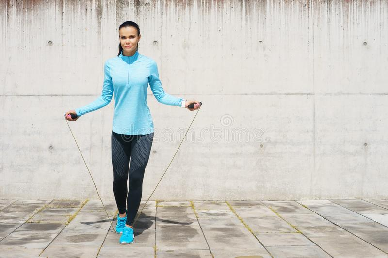 Young, fit and sporty woman jumping with a skipping rope. Fitness, sport, urban jogging and healthy lifestyle concept. Young, fit and sporty girl jumping with a stock photos