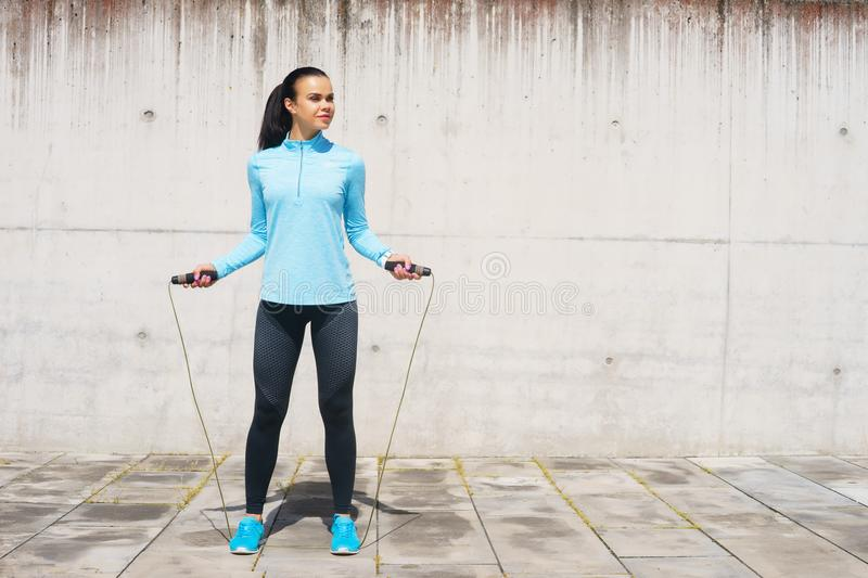 Young, fit and sporty woman jumping with a skipping rope. Fitness, sport, urban jogging and healthy lifestyle concept. Young, fit and sporty girl jumping with a stock images