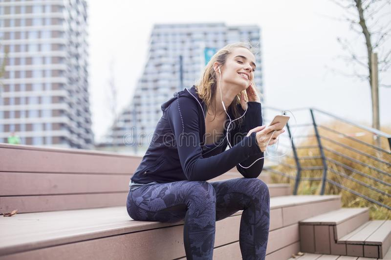 Young fit sporty woman resting and listen music on mobile phone stock photo