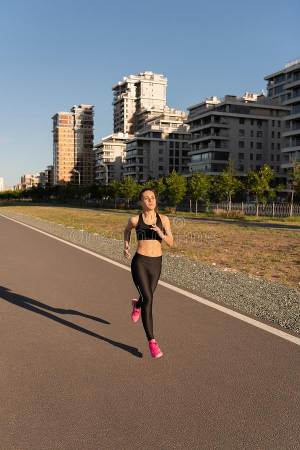 Sportive female jogging on track stock photos