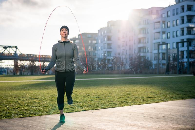 Young fit woman burning calories through alternate jumping. Full length of a young fit woman burning calories through alternate jumping over the skipping rope royalty free stock photography