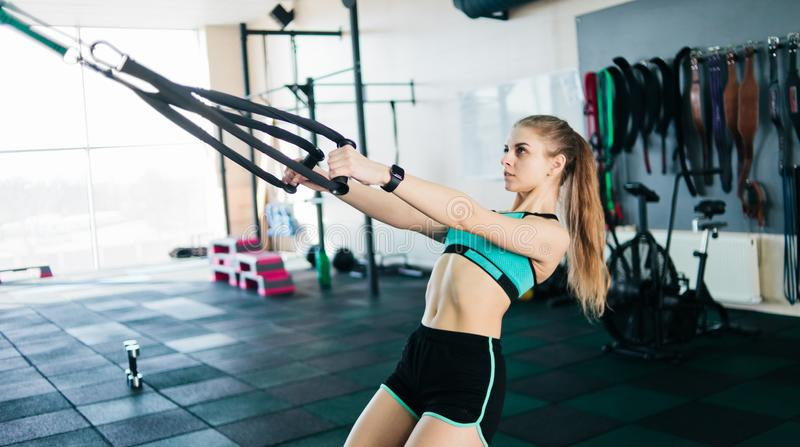 Sport. Young fit woman doing exercise with fitness straps in the gym. Functional training. Sports lifestyle royalty free stock image