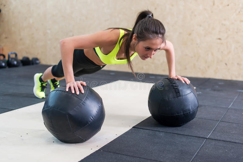 Young fit woman doing push up on medicine ball at gym. stock photography