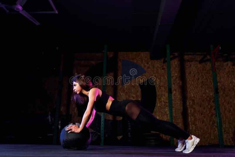 Young fit woman doing push up or plank exercise on medicine ball at gym royalty free stock photos